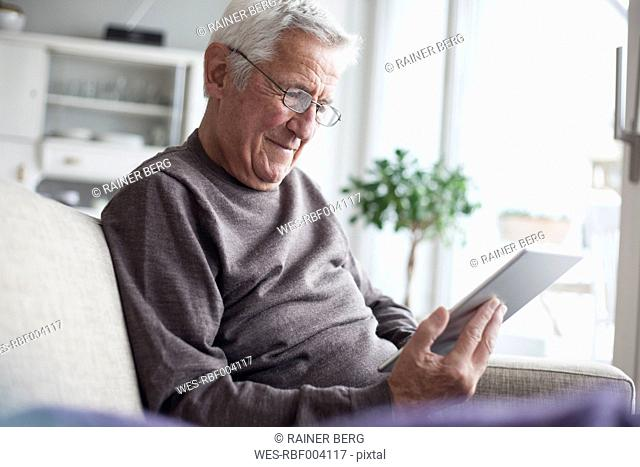 Portrait of senior man sitting on couch at home using digital tablet