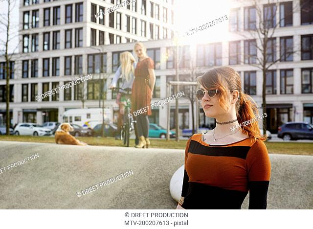 Close-up of a young woman and her friends in the background, Munich, Bavaria, Germany