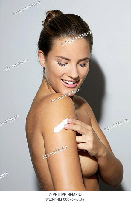 Smiling beautiful young woman applying skin cream on her arm