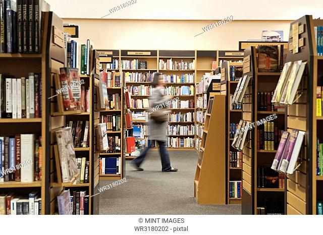 Caucasian female browsing through books in a bookstore