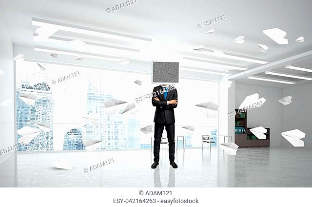 Businessman in suit with monitor instead of head keeping arms crossed while standing among flying paper planes inside office building. 3D rendering