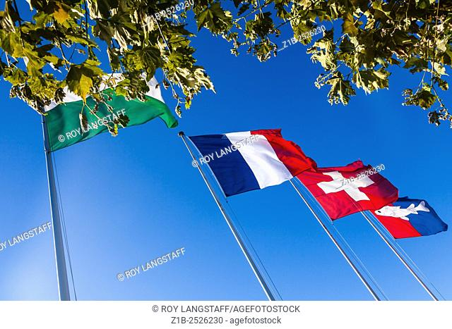 Flags of the Canton Vaud, France, Switzerland, and the coat of arms of Nyon by the ferry dock at Nyon