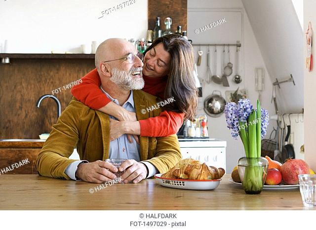 Happy couple embracing and smiling by table at home