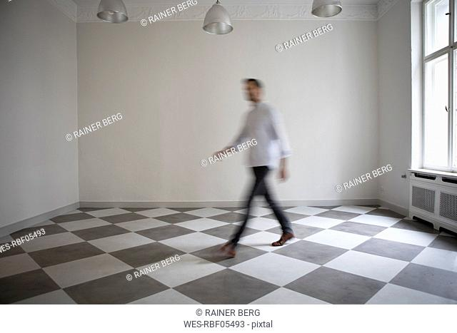 Man crossing empty room of an apartment