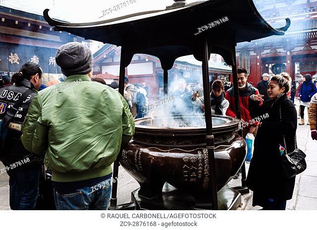 People making offerings around big incense burner in Sensoji temple, Tokyo, Japan