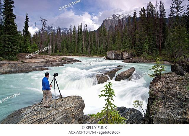 A photograper takes his shot while over The Natural Bridge and the Kicking Horse River at Yoho National Park, near Field, Rocky Mountain region