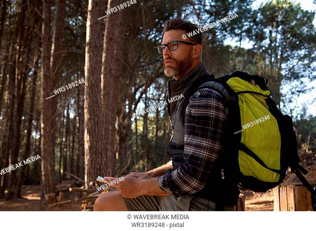 Man with backpack standing in forest