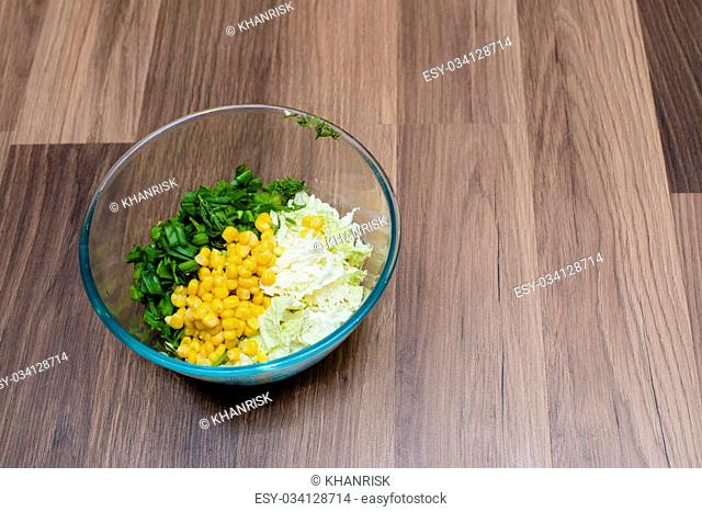 cabbage, corn , herbs in a plate of glass on a wooden table
