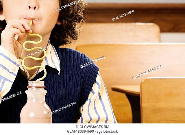 Schoolboy drinking chocolate milkshake in a classroom