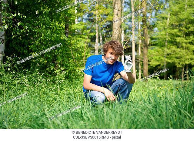 Smiling boy retrieving golf ball