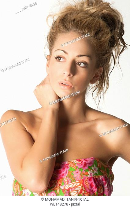 Beautiful young woman hand touching neck looking away against a white background