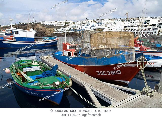 PUERTO DEL CARMEN LANZAROTE Fishing boats alongside quayside in old town harbour marina