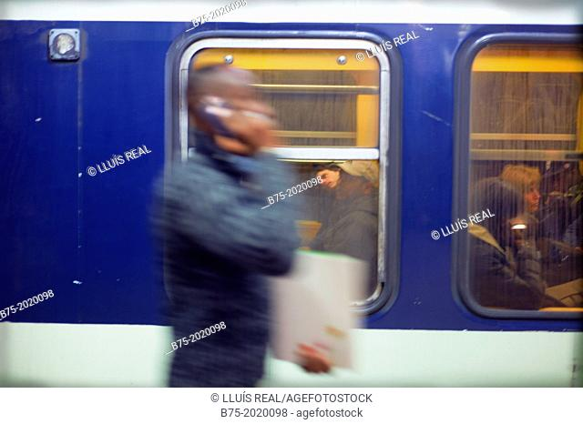 Unrecognizable young man in motion, walking and talking on the phone on the platform of a Paris metro station, France