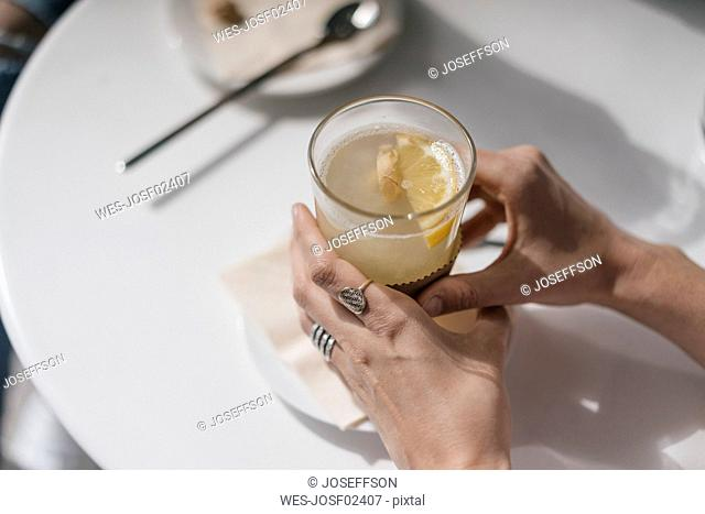 Woman holding glass of ginger lemon tea
