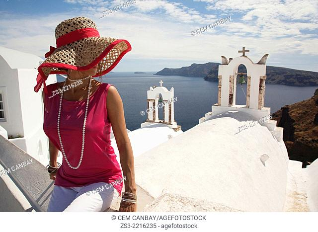 Woman in front of a bell tower in Oia town looking at Caldera, Santorini, Cyclades Islands, Greek Islands, Greece, Europe