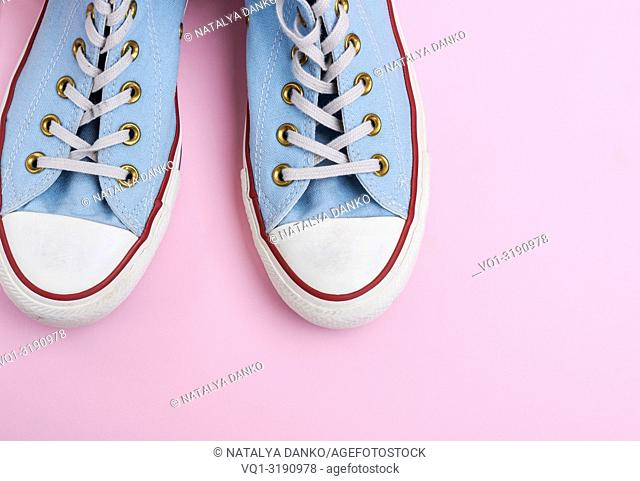 pair of old worn blue sneakers with white laces on a pink background, top view