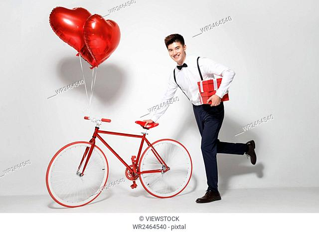 Young man with bicycle and balloons