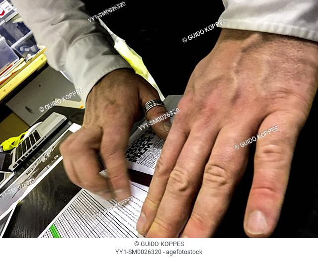 Tilburg, Netherlands. Hands en Fingers of a young adult caucasian male searching sheets with chemical info for the right numbers