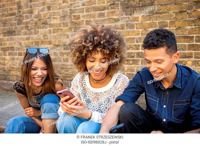 Three friends sitting in street, looking at smartphone