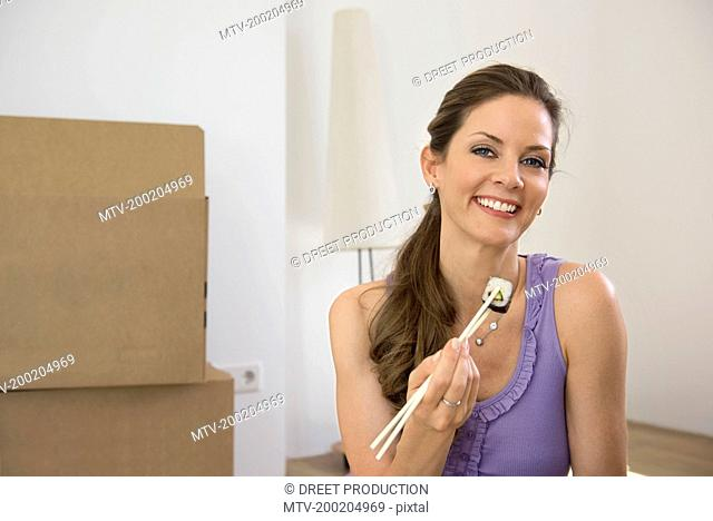 Woman alone moving home eating Sushi