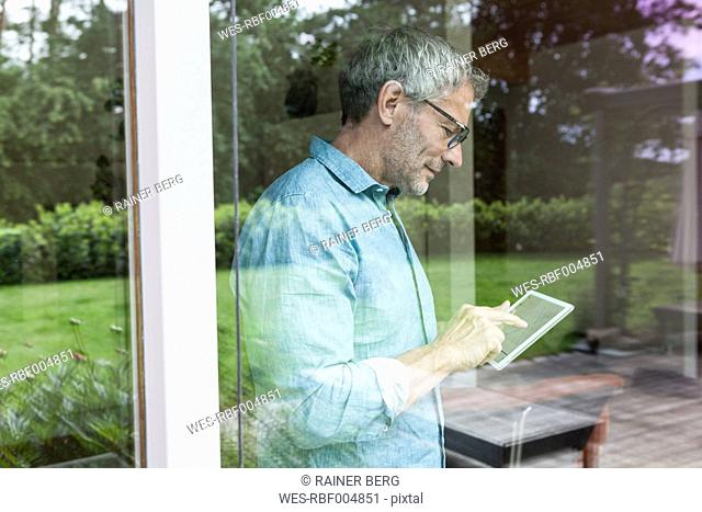 Mature man using digital tablet behind windowpane