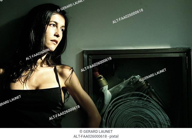 Woman in dress leaning against wall next to fire hose, looking away