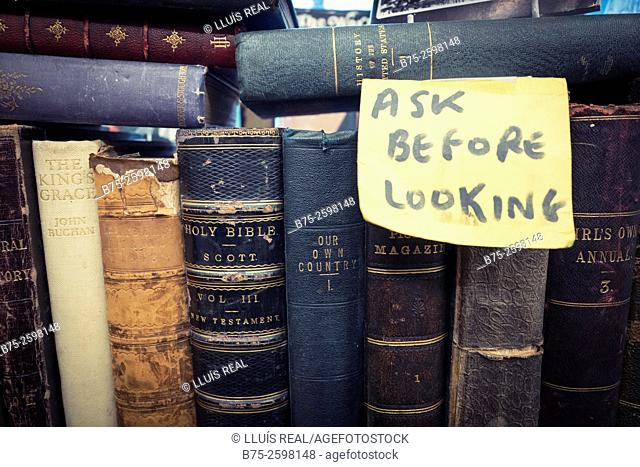 'Ask before looking', written on a paper stuck in a group of old books in a Old Book Shop. England, UK, Europe