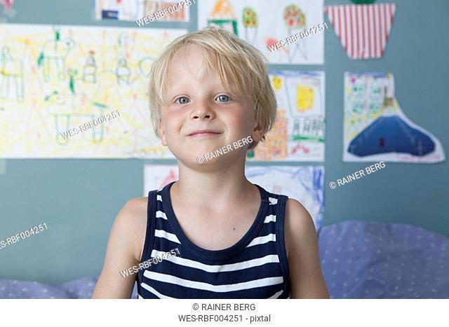 Portrait of confident little blond boy at children's room