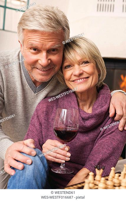 Germany, Kratzeburg, Senior couple with wine glass and chess board