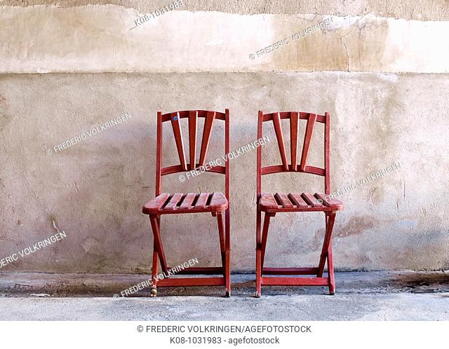 Two red folding chairs against wall