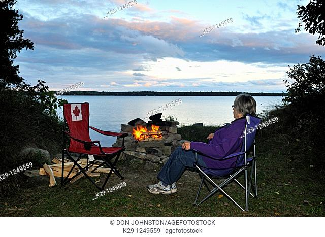 Woman sitting and enjoying the campfire beside Kagawong Lake, Manitoulin Island