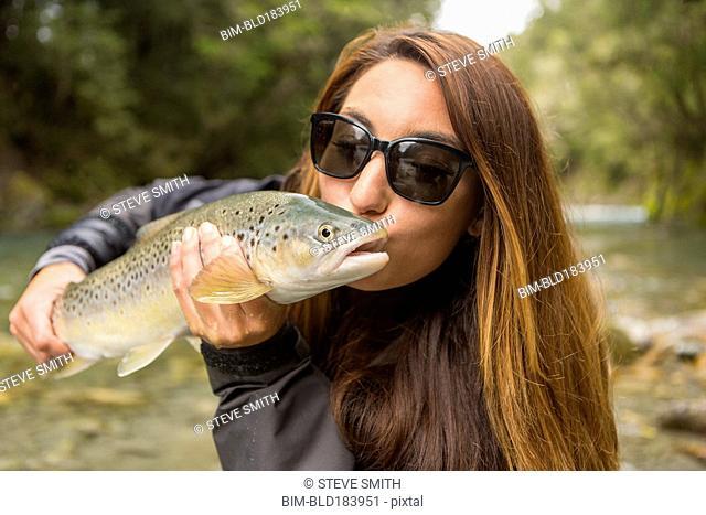 Caucasian woman kissing fish in remote river