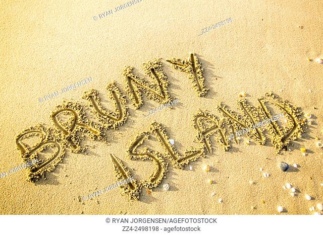 Tasmania travel destinations concept with the words Bruny Island hand drawn into the surface of sand