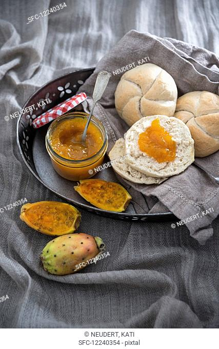 Homemade vegan prickly pear jam with crusty bread roll halves