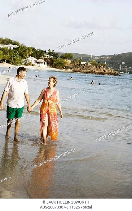 Mature woman holding a senior man's hand and walking on the beach