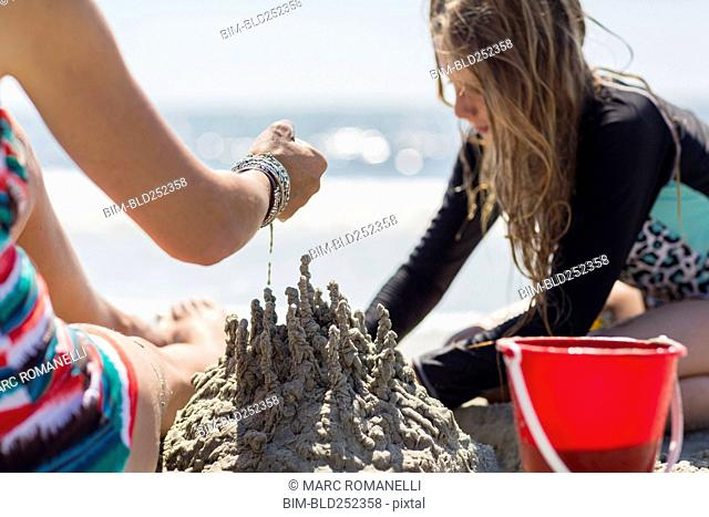 Caucasian mother and daughter playing with sand castle at the beach