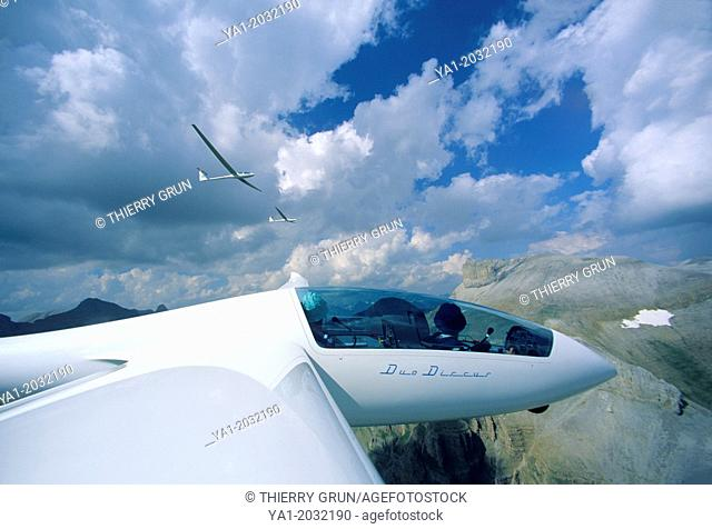 Glider plane Duo Discus flying with two others over Pyrenees mountains, north of Jaca, Aragon, Spain