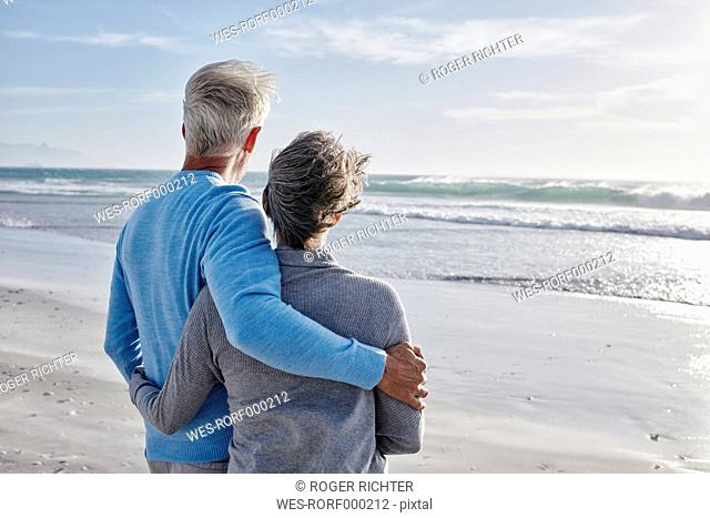 Back view of couple on the beach looking to the sea
