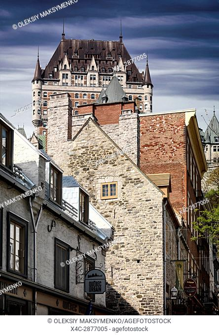 Low angle view of Fairmont Le Château Frontenac through the rooftops of historic buildings on rue Sous le Fort, grand hotel Chateau Frontenac