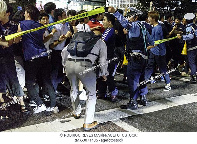 Tokyo Metropolitan Police restraints Japanese soccer fans access to Shibuya's famous scramble after their team advanced to the second round of World Cup on June...