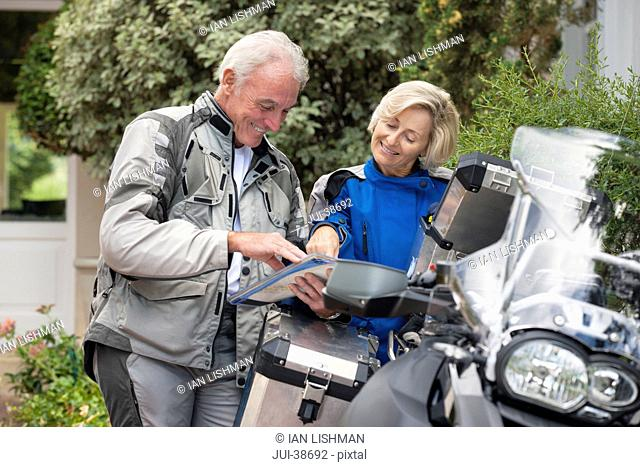Smiling senior couple looking at map next to motorcycle