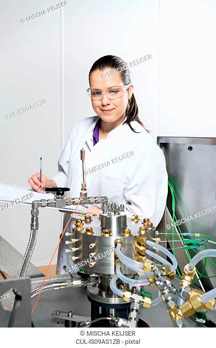 Portrait of female scientist, doing research on a innovative technology for mixing chemicals, at a hightech startup company