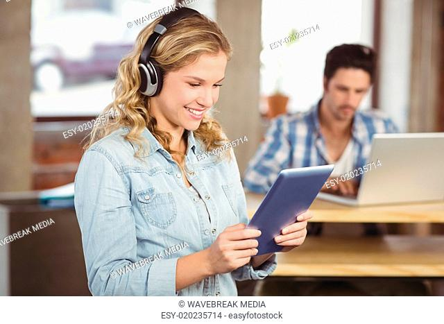 Woman holding digital tablet while colleague working on laptop in office