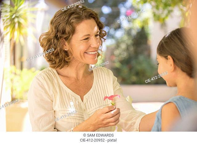 Grandmother offering granddaughter pink flower