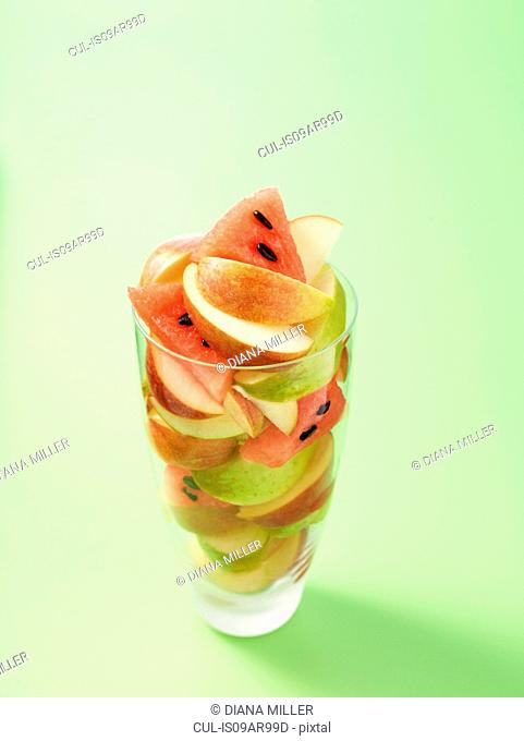 Glass full of apple and melon slices on light green background