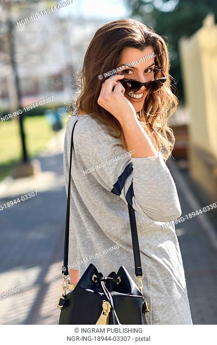 Portrait of beautiful woman looking over her sunglasses in urban background