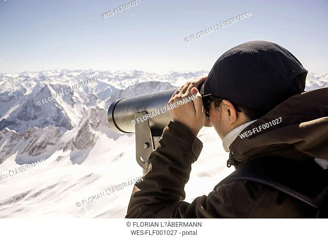 Germany, Bavaria, woman looking through telescope at Zugspitze