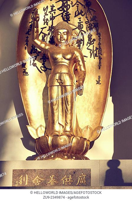 Sunlit standing golden Buddha figure, Battersea Park Peace Pagoda, London, England, Europe