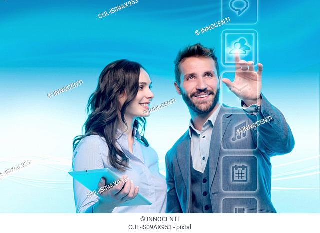 Man and woman using graphical screen, man touching icon