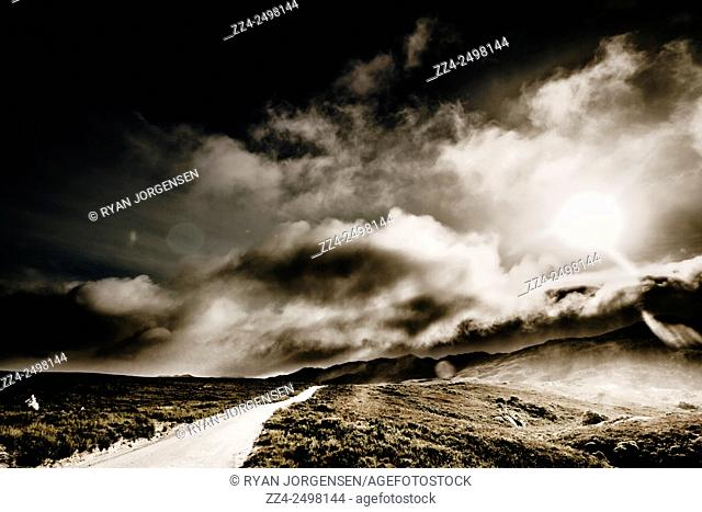 Dramatic dark path leading through a vast space of storm covered turbulence. Road from Trial Harbour to Zeehan, Tasmania, Australia